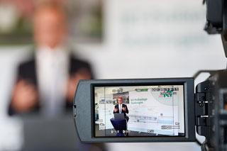 Monitor eines Camcorders zeigt Mann bei Vortrag