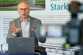 Mann mit Brille vor Laptop gestikuliert