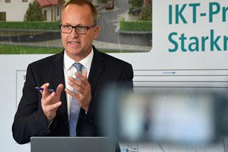 Mann mit Brille und Anzug gestikuliert bei Vortrag