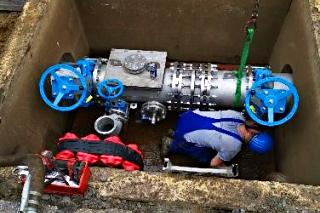 Schacht zu einer Abwasserdruckleitung mit Armaturen und blauen Handrädern