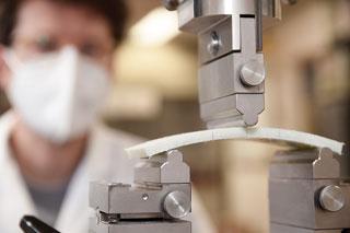 Materialprobe auf Prüfgerät, Mann mit Atemschutzmaske im Hintergrund