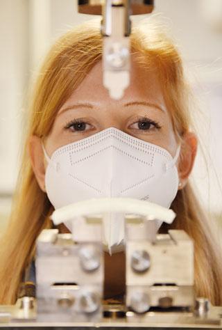 Portrait einer rothaarigen Frau mit Atemschutzmaske, davor Prüfapparatur