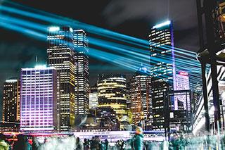 Skyline bei Nacht mit blauen Laserstrahlen