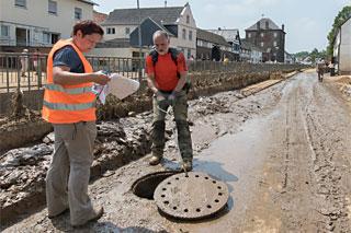 Personen in Arbeitskleidung an geöffnetem Abwasserschacht