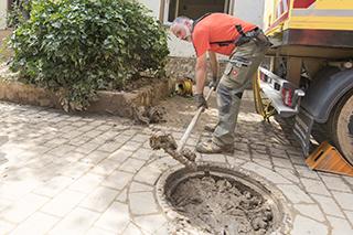 Mann schaufelt Schlamm aus dem Schmutzfang eines Abwasserschachts